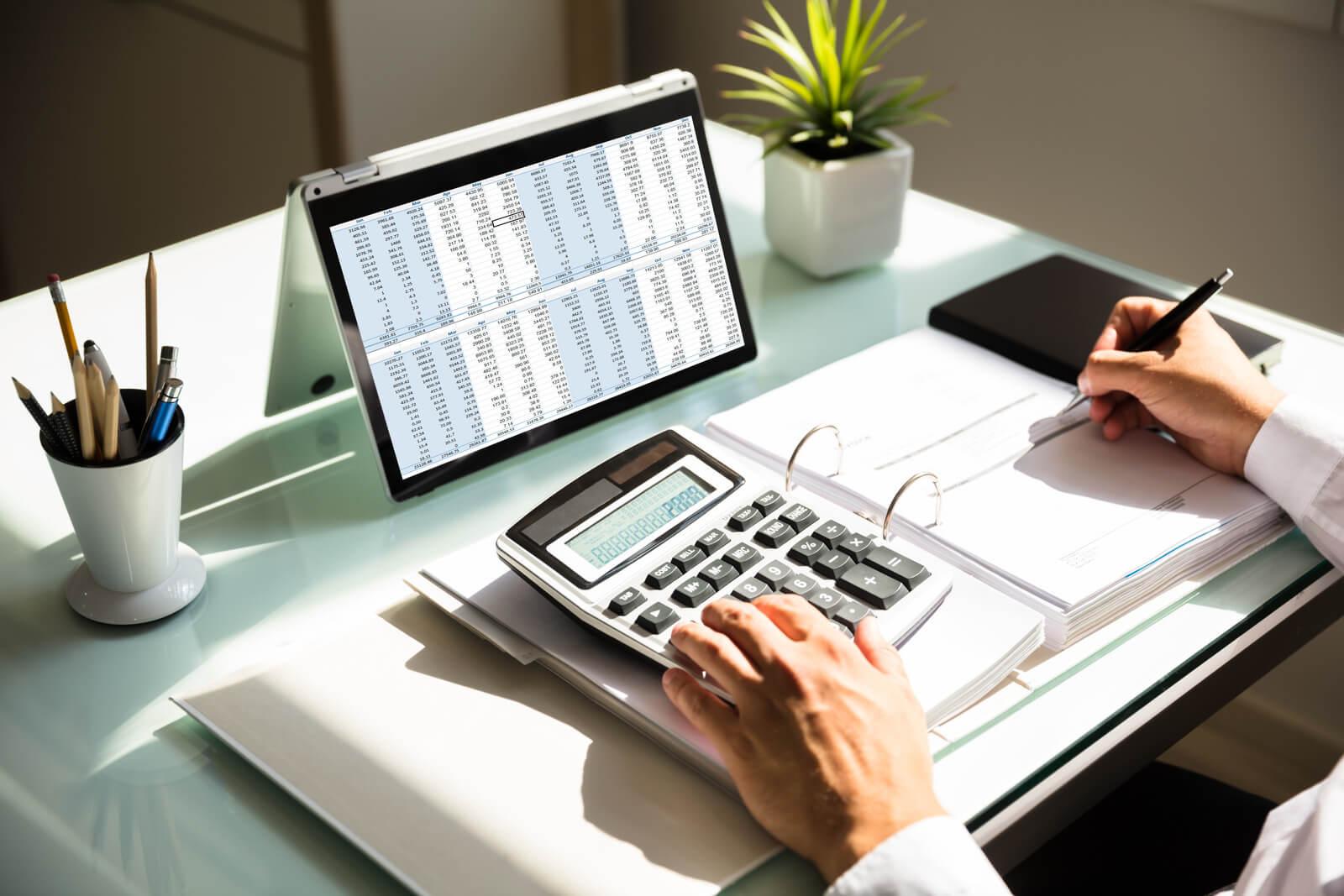 Businessman calculating invoice using calculator